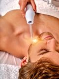 Young man receiving electric facial massage. High frequency machine in spa salon. Young man receiving electric darsonval facial massage after procedure at stock photography