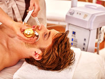 Young man receiving electric facial massage. Royalty Free Stock Photo