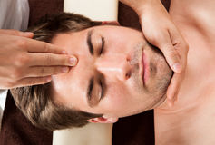 Young Man Receiving Forehead Massage In Spa Stock Photos