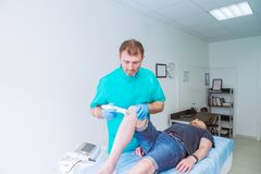 Young man receiving laser or magnet therapy massage on a knee to less pain. A chiropractor treats patient`s knee-joint in medical royalty free stock photography