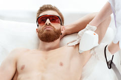 Young man receiving laser skin care on armpit isolated on white Stock Photos