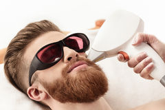 Young man receiving laser skin care on face isolated on white Stock Photography