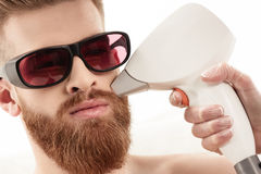 Young man receiving laser skin care on face isolated on white Royalty Free Stock Images