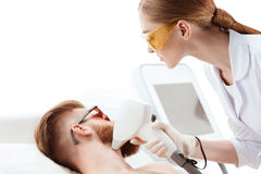 Young man receiving laser skin care on face isolated on white Royalty Free Stock Photos