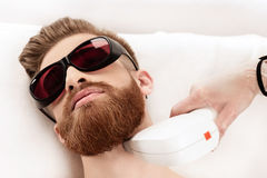 Young man receiving laser skin care on neck Royalty Free Stock Photos