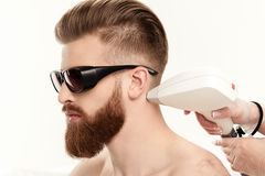 Young man receiving laser skin care on neck isolated on white Royalty Free Stock Photos