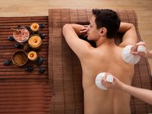 Young man receiving massage with stamps in spa Stock Photo