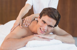 Young man receiving shoulder massage at spa center Stock Photography