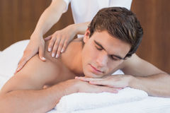 Young man receiving shoulder massage at spa center Stock Photos