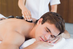 Young man receiving stone massage at spa center Stock Photo