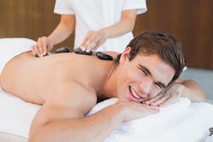 Young man receiving stone massage at spa center Royalty Free Stock Image