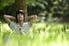 Young man reclining against tree, hands behind head, ground view Stock Photography