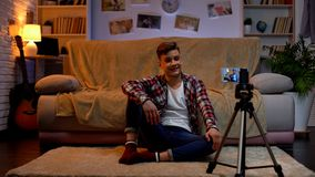 Young man recording video on smartphone at home, going to become blogger, hobby. Stock photo stock images