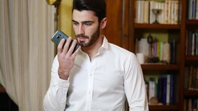 Young man recording voice message on cell phone. Attractive young man recording voice message on cell phone while standing at home, with serious expression stock video footage
