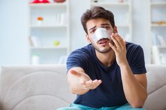 Young man recovering healing at home after plastic surgery nose Stock Photo