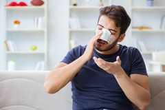 Young man recovering healing at home after plastic surgery nose Stock Images