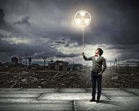 Young man with a recycle symbol. Against a polluted and ruined landscape Royalty Free Stock Photos