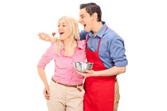 Young man in a red apron feeding his girlfriend Stock Images