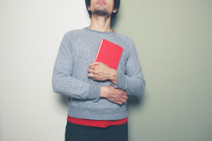 Young man with red book against split colored background Royalty Free Stock Photo