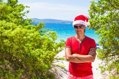 Young man in red christmas Hat on tropical beach Stock Photography