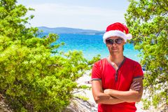 Young man in red christmas Hat on tropical beach Royalty Free Stock Image