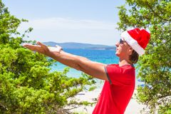 Young man in red christmas Hat on tropical beach Stock Image