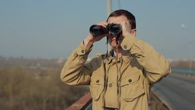 Young man with red hair in in khaki coat looking through binoculars from the bridge. Morning. Spring. Fog stock video