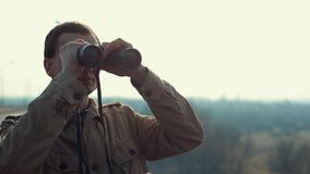 Young man with red hair in in khaki coat looking through binoculars from the bridge. Morning. Spring. Fog stock video footage