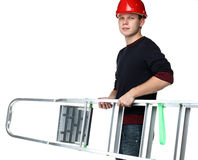 Young man in red hard hat holding stepladder Stock Image
