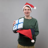 Young man in red hat. Amazed young man in christmas red hat open present on grey background Royalty Free Stock Photo