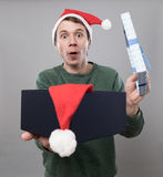Young man in red hat. Amazed young man in christmas red hat open present on grey background Royalty Free Stock Photos