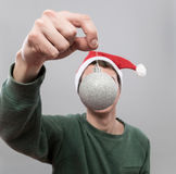 Young man in red hat. Young man in christmas red hat holding decoration silver ball on grey background Stock Images