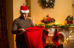 Young man in red hat looking inside of Santa bag with amazement Royalty Free Stock Photos