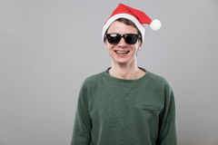 Young man in red hat. Portrait of an amazed young man in christmas red hat and wearing sunglasses on grey background Royalty Free Stock Image