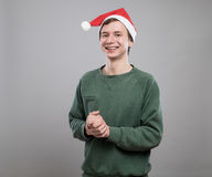 Young man in red hat. Smiling young man in christmas red hat on grey background Stock Images