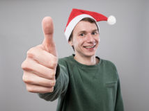 Young man in red hat. Smiling young man in christmas red hat with thumb up on grey background Royalty Free Stock Image