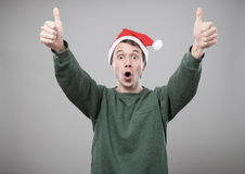 Young man in red hat. Smiling young man in christmas red hat with thumbs up on grey background Stock Photos