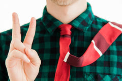 Young man with red necktie shows victory sign Stock Images