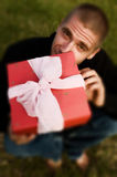 Young man with a red present. Young caucasian man with a red present and pink ribbon Royalty Free Stock Photo