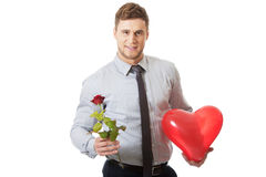 Young man with a red rose and heart balloon. Royalty Free Stock Photos