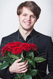 Young man with a red roses. Young handsome man dressed in a black suit with a bouquet of a red roses Stock Images