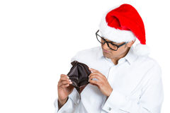 young man in red santa claus hat with big black glasses holding up showing empty wallet Royalty Free Stock Photos