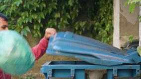 Young Man in Red Sportswear Throwing Away Rubbish. Close-up shot Stock Image