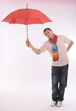 Young man with a red umbrella Stock Photography