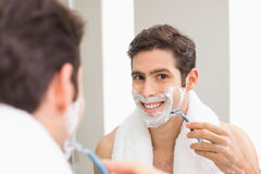 Young man with reflection shaving in bathroom. Close up of a handsome young man with reflection shaving in the bathroom Stock Photos