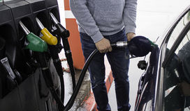 Young man refueling gasoline in a car stock photography