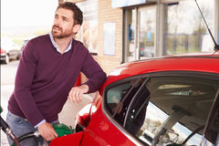 Young man refuelling a car at a petrol station Royalty Free Stock Images