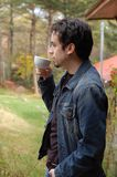 Young Man Relax. A young man enjoys and having a cup of coffee outdoors Royalty Free Stock Image