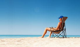 Young man relax with e-book on white sand beach Stock Photos