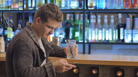 Young man relax and using a smartphone in a bar. Young man with mustache sits near a bar. His left hand lays on a bar and holds a glass with liquid. Handsome man stock footage